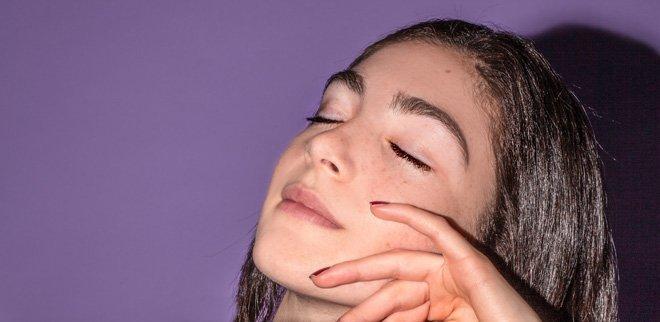 Junge Frau mit geschlossenen Augen berührt ihre Wange