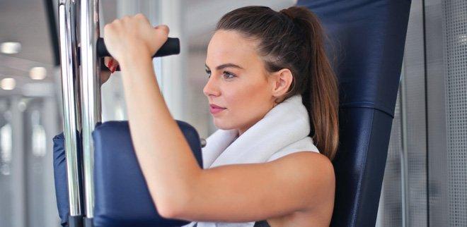 Frau trainiert an einem Fitnessgerät