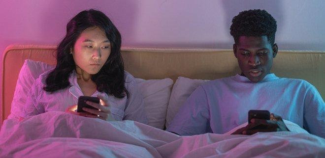 Couple assis dans un lit avec un téléphone portable, elle louche sur son écran.
