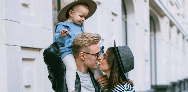 Junge Eltern mit Kind auf den Schultern küssen sich
