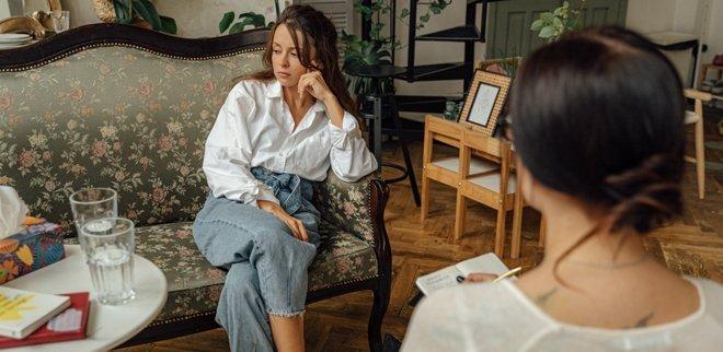 Junge Frau sitzt im Zimmer einer Therapeutin