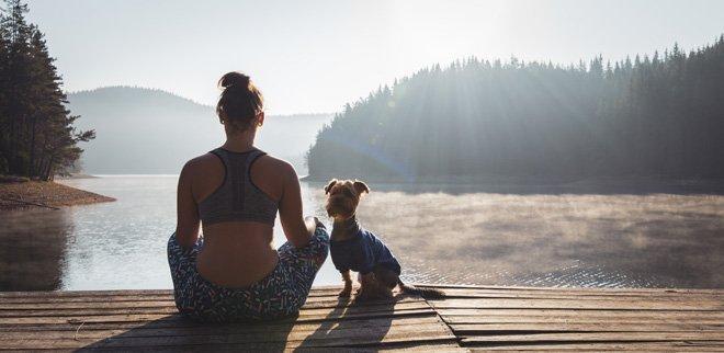 Meditierende Frau am See mit Hund.
