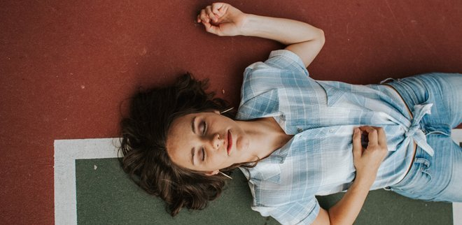Frau mit geschlossenen Augen auf einem Sportfeld liegend