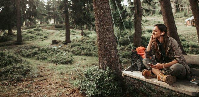 Frau auf Sitzbank im Wald